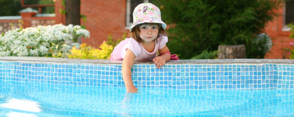 A toddler girl leaning over the edge of a pool to touch the water