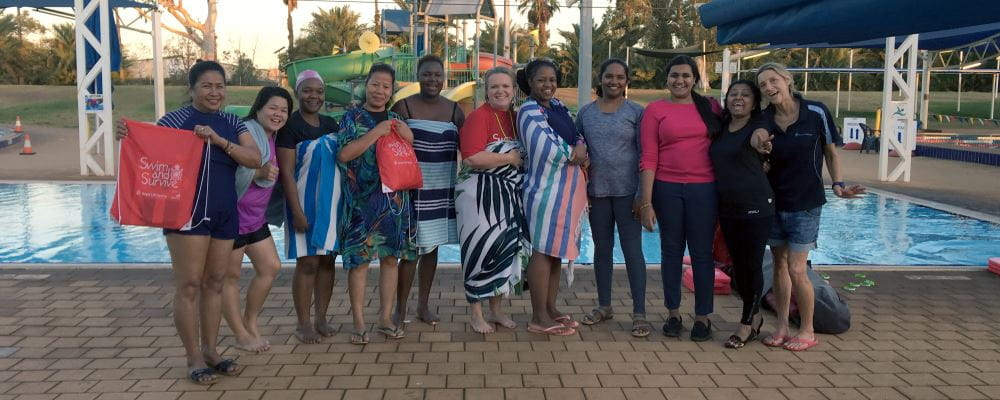 Multicultural women with their swim instructor and Royal Life Saving mentor holding red Swim and Survive bags by the pool at South Hedland