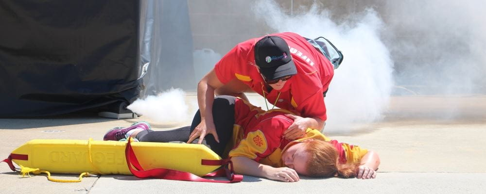 A lifeguard attending to a person passed out on the ground with smoke in the background
