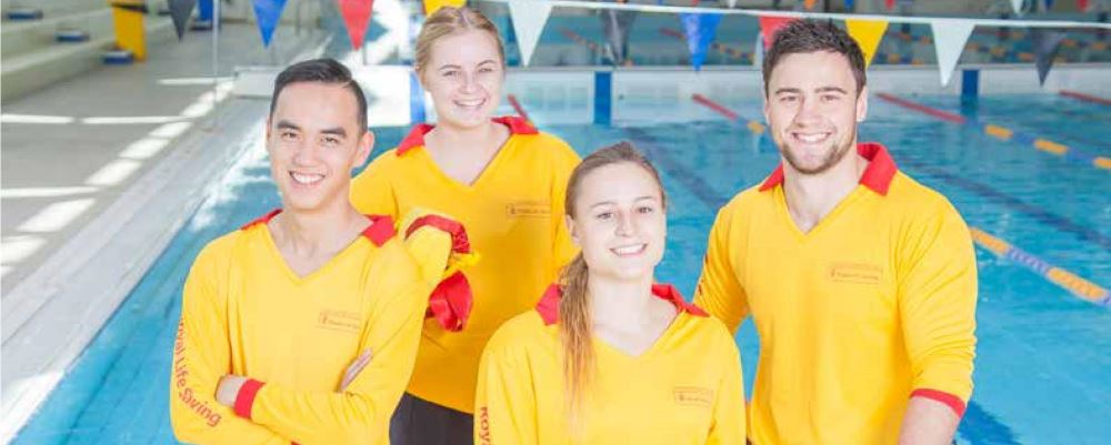 Image of four lifeguards standing by a pool smiling at the camera