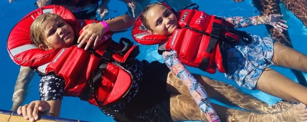Two Aboriginal girls in the pool wearing red lifejackets