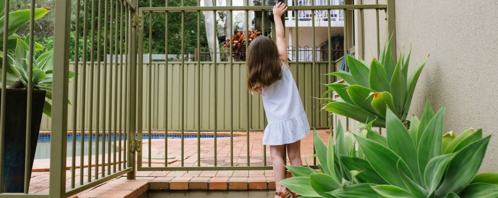A little girl at a pool gate, reaching up for the latch