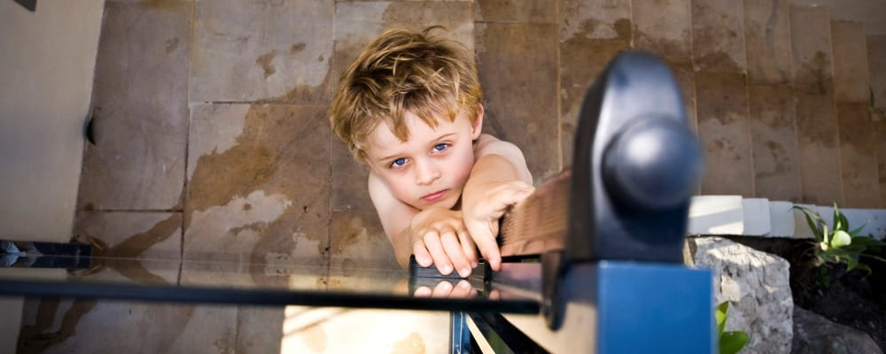 image of young boy reaching up to pool gate latch and looking at camera