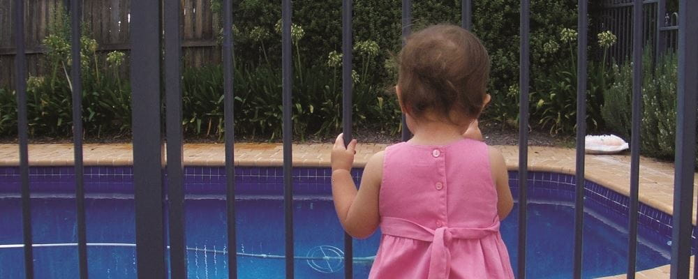 image of toddler girl holding on to pool gate and looking at pool
