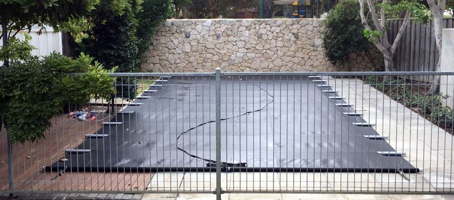 A home pool covered with amn Elite Pool Cover and guarded by a fence.