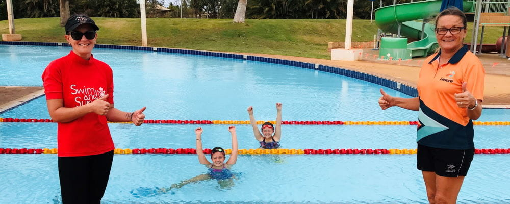 Two swim instructors by the pool with two children in the water at South Hedland Aquatic Centre