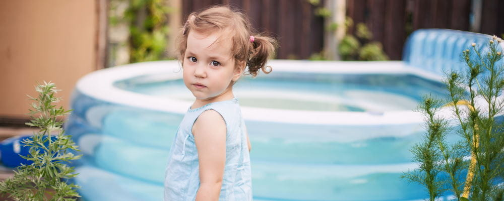 A toddler girl standing by a portable pool in a backyard