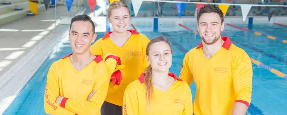 A group of 4 lifeguards standing by a pool