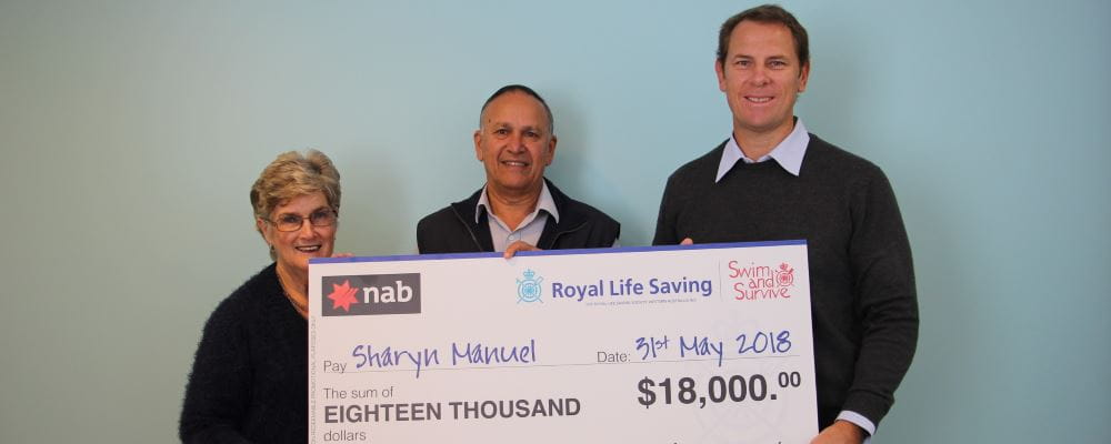 Raffle winner Sharyn Manuel with husband Neil and RLSSWA CEO Peter Leaversuch, holding a giant winners cheque