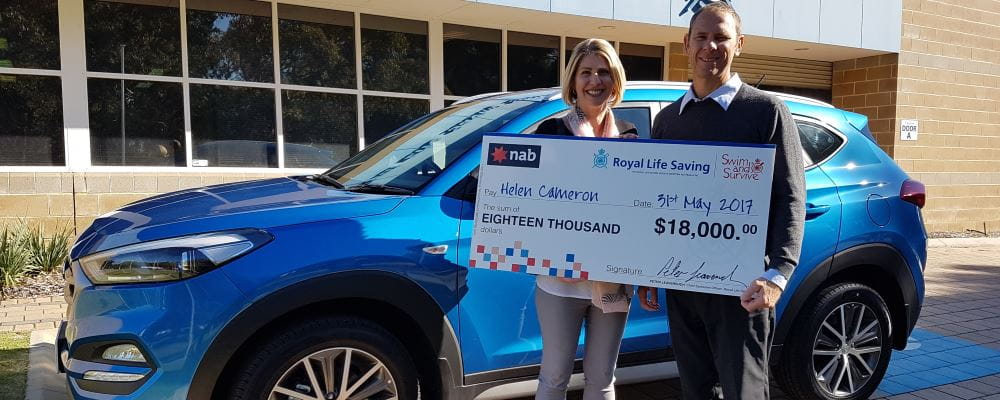 Raffle winner Helen, with Royal Life Saving Society WA CEO Peter Leaversuch, holding a giant cheque and standing in front of Helen's brand new blue Hyundai Tucson