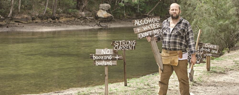 A man wearing a flannel shirt and holding an axe with signs warning about the dangers of alcohol and water
