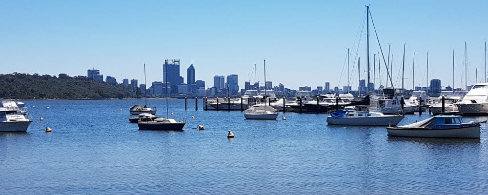 An image of the Swan River with boats in the foreground and the Perth city skyline in the distance