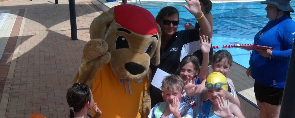 Rodena Lightbody with Walter the Watchdog and a group of children at Bruce Rock pool