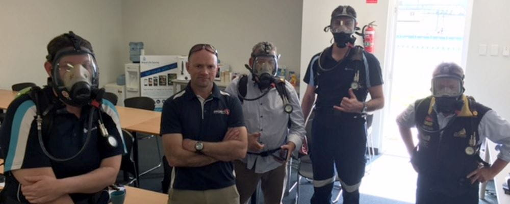 Four Royal Life Saving staff with their Priority 1 trainer wearing SCBA masks