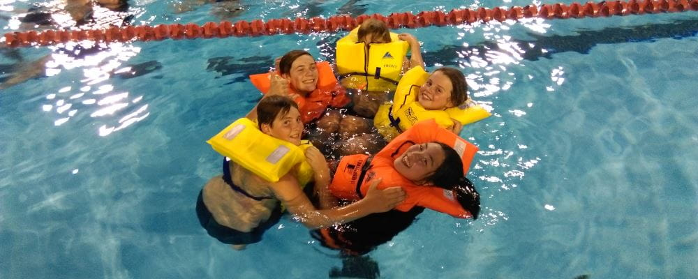 Image of 5 Scouts wearing lifejackets and completing a safety exercise in the pool