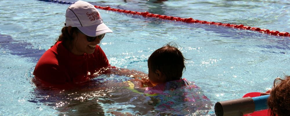 image of a swim instructor with an infant in a swimming class