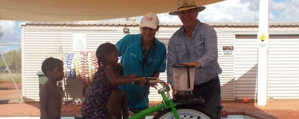 image of children trying out the Smoothie Bike with pool manager Jacqui Forbes and Anthony Holman from EON Foundation