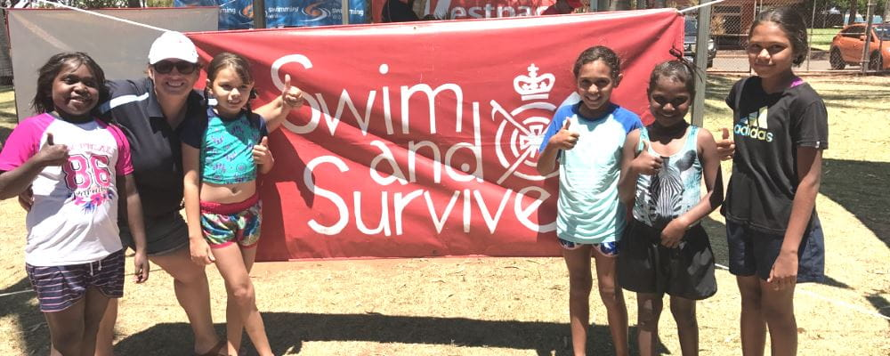 Swim School Coordinator Raelene Leeds with 5 aboriginal girls and a Swim and Survive sign at the Spirit Carnival