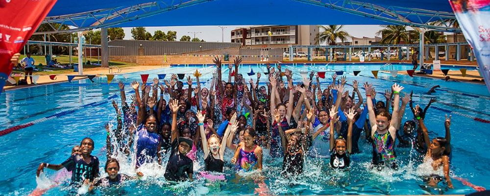 A group of children in the pool at South Hedland aquatic centre, jumping up with arms in the air