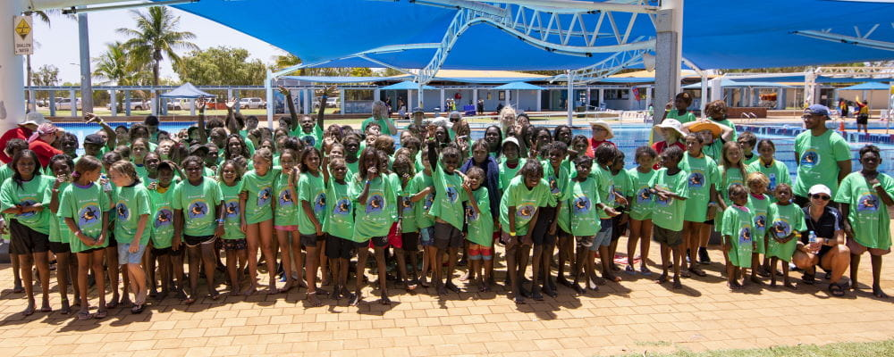 A group of aboriginal children with thier swim instructors and teachers, wearing green Spirit Carnival t-shirts by the pool at Port Hedland