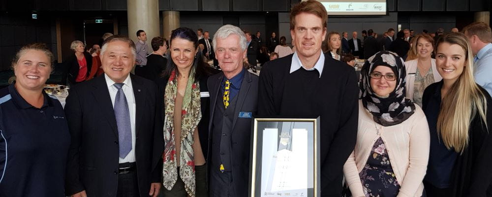 Trent Hotchkin holds the Sport and Recreation Industry Leadership award surrounded by members of the multicultural steering committee