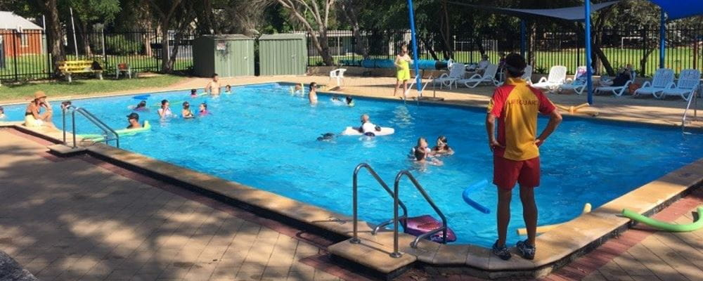 A Lifeguard supervises a number of kids in a pool on a lovely summer's day.
