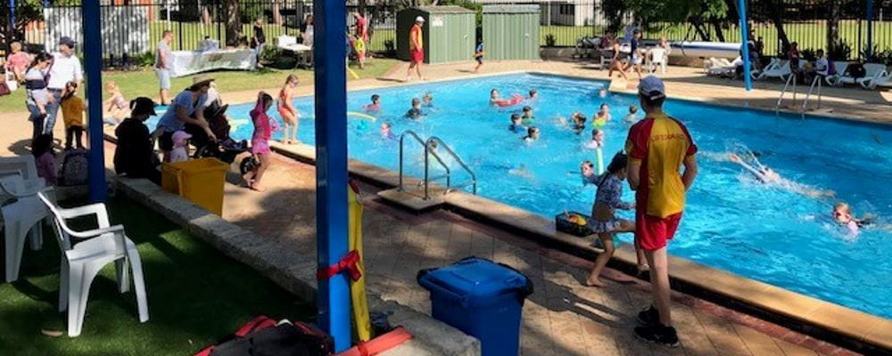 Children swimming in the pool at Subiaco Primary School while a lifeguard looks on