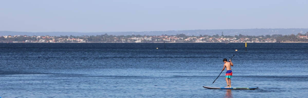 A young SUP paddle boarder cruises down the calm swan river