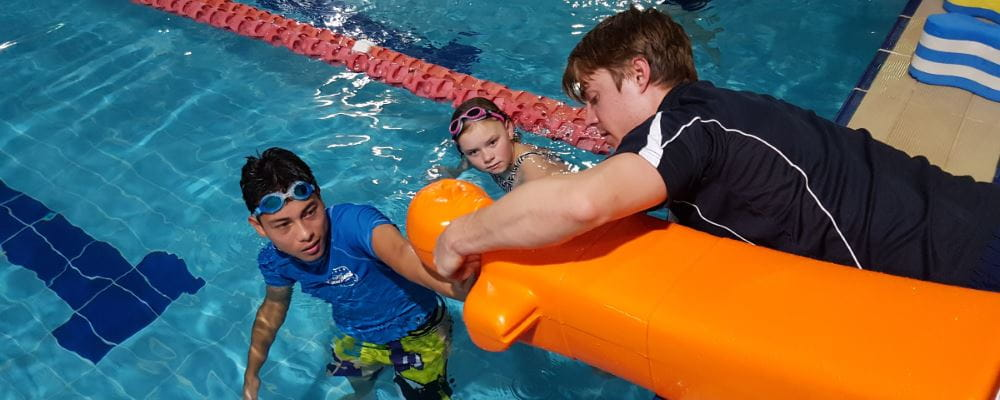 A lifeguard trainer showing two children how to tow a lifesaving manikin