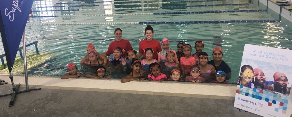 A group of multicultural girls in the water with two instructors smiling at the camera