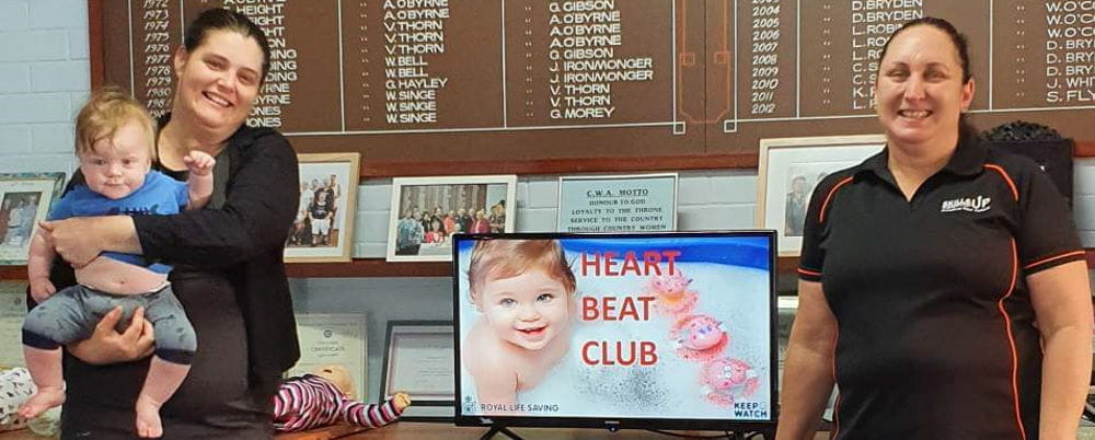 A heart beat club presentation with two women by a computer screen, one holding a baby