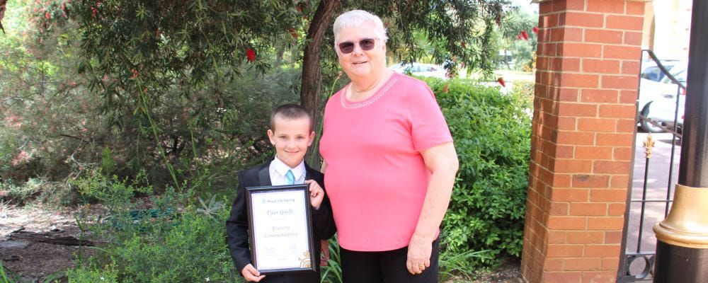 Tyler Guelfi with family friend Dale Bolin holding his Royal Life Saving Bravery Award outside Government House