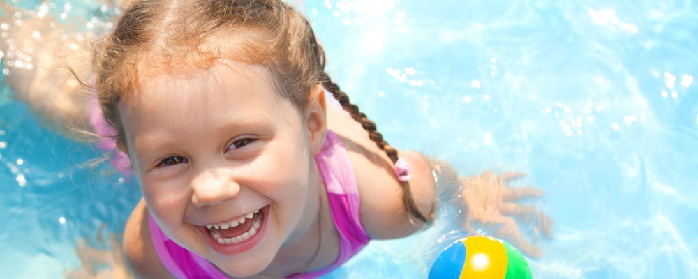 A toddler girl in a pool, smiling up at the camera