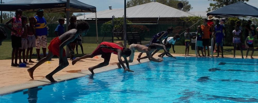image of aboriginal children swimming in a race