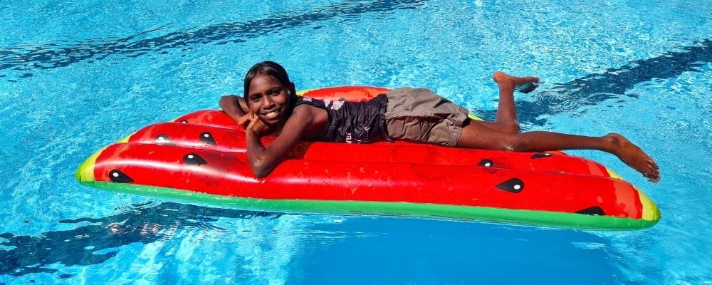 An Aboriginal girl laying in a watermelon inflatable in a pool