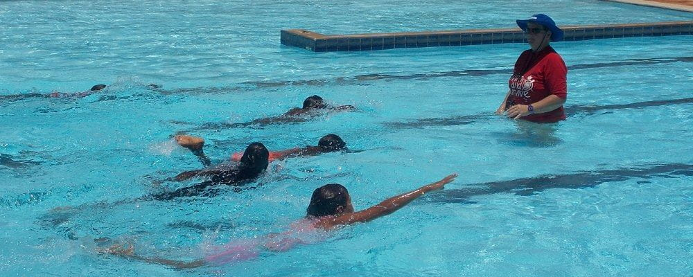 image of children swimming laps with instructor looking on