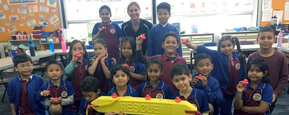 Children from parkwood Primary School with their Royal Life Saving water safety instructor holding a rescue tube