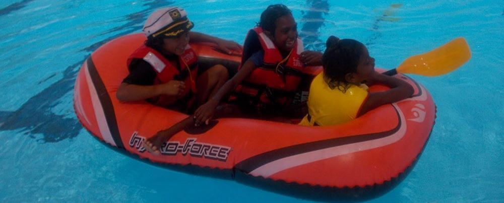 Three aboriginal children in a boat in the pool