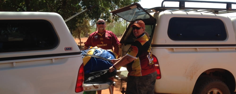 remote pool managers Trevor Caporn and Bernie Egan transfering the Watch Around Water inflatable between their cars in remote WA