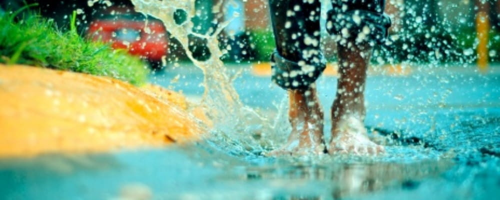 image of a person's feet splashing in a puddle