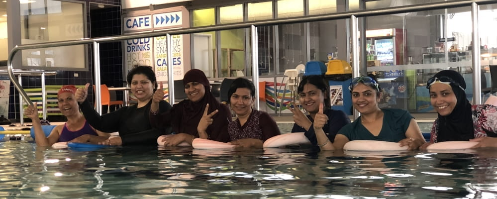 A group of multicultural women partake in the swim and survive swimming lessons