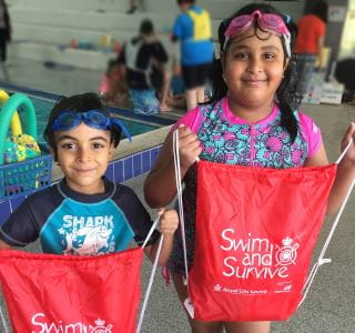 Two multicultural children by the pool at Bayswater Waves, holding Swim and Survive bags