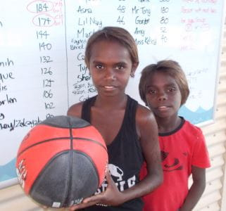 Two aboriginal boys with a basketball in front of the Go For 2 and 5 Tally Board at Bidyadanga