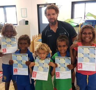 Five aboriginal children with thier swimming certificates and Burringurrah pool manager Aaron