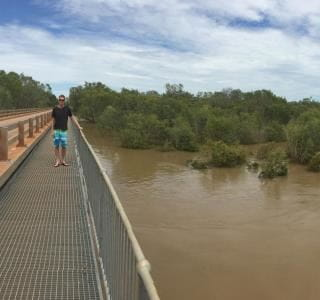RLSSWA's Greg Tate standing on a bridge by a very swollen Fitzroy River