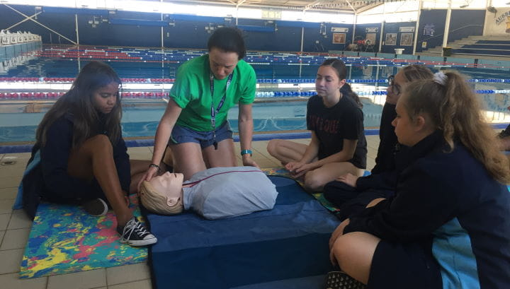 Four girls from Geraldton girls academy with an instructor demonstrating on a CPR manikin by the pool