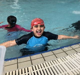An islamic boy in the pool wearing a swimming cap and goggles, with arms out to the side smiling