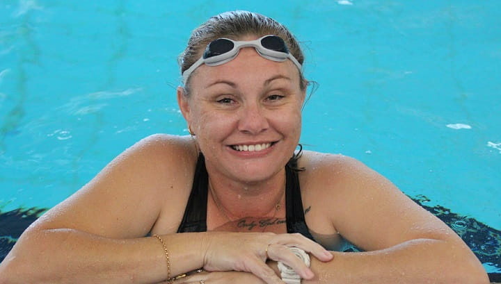 Swim Instructor Marianne Mallard smiling from the edge of swimming pool