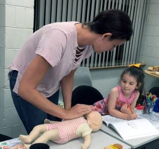 A mum doing CPR on a baby manikin with her toddler daughter looking on