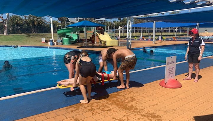 A group of trainees lifting someone out of a pool on a spineboard while a trainer looks on